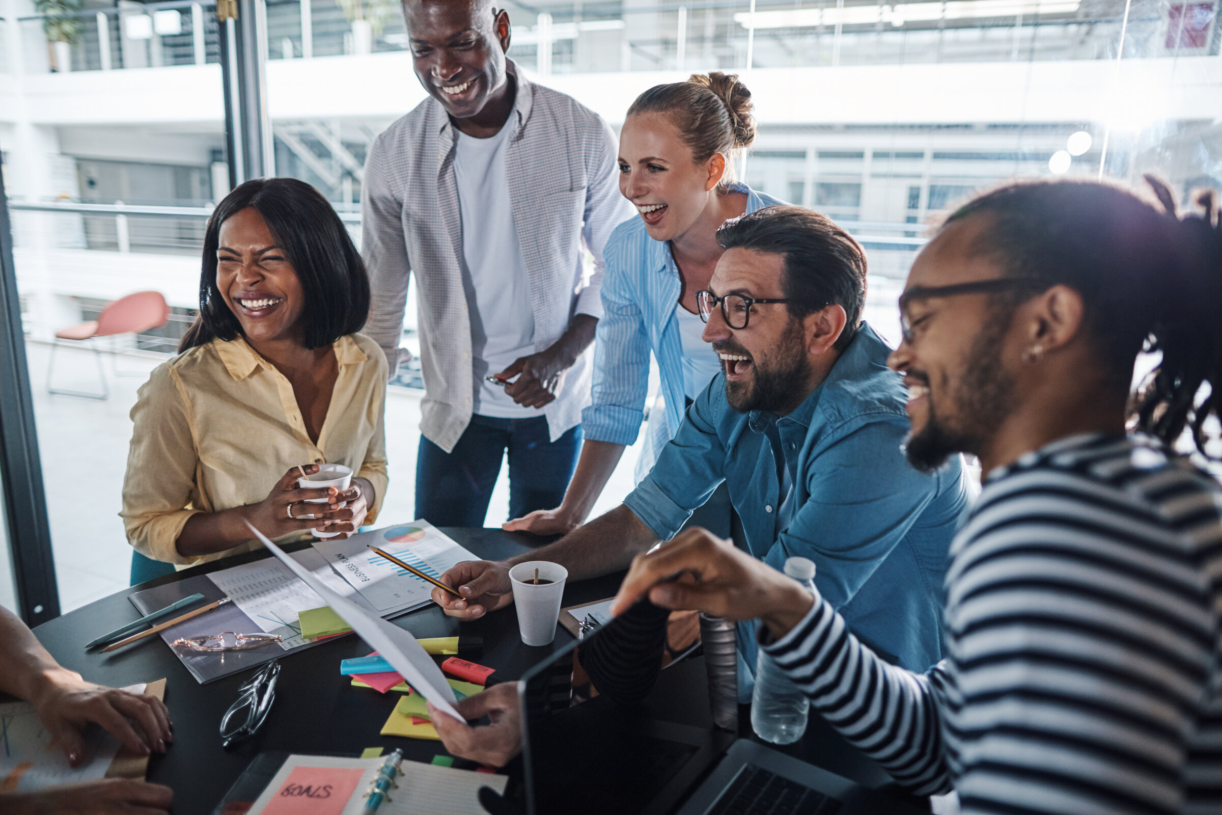Laughing group of diverse businesspeople having an office meeting together